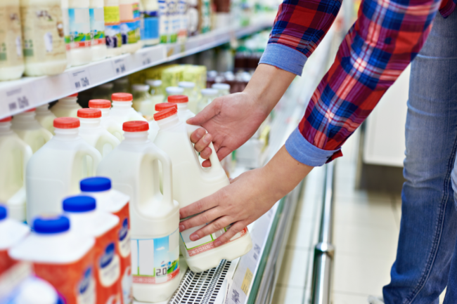 Shopper buying milk at grocery store